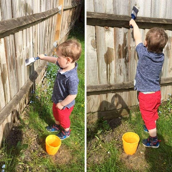 kid painting fence with water