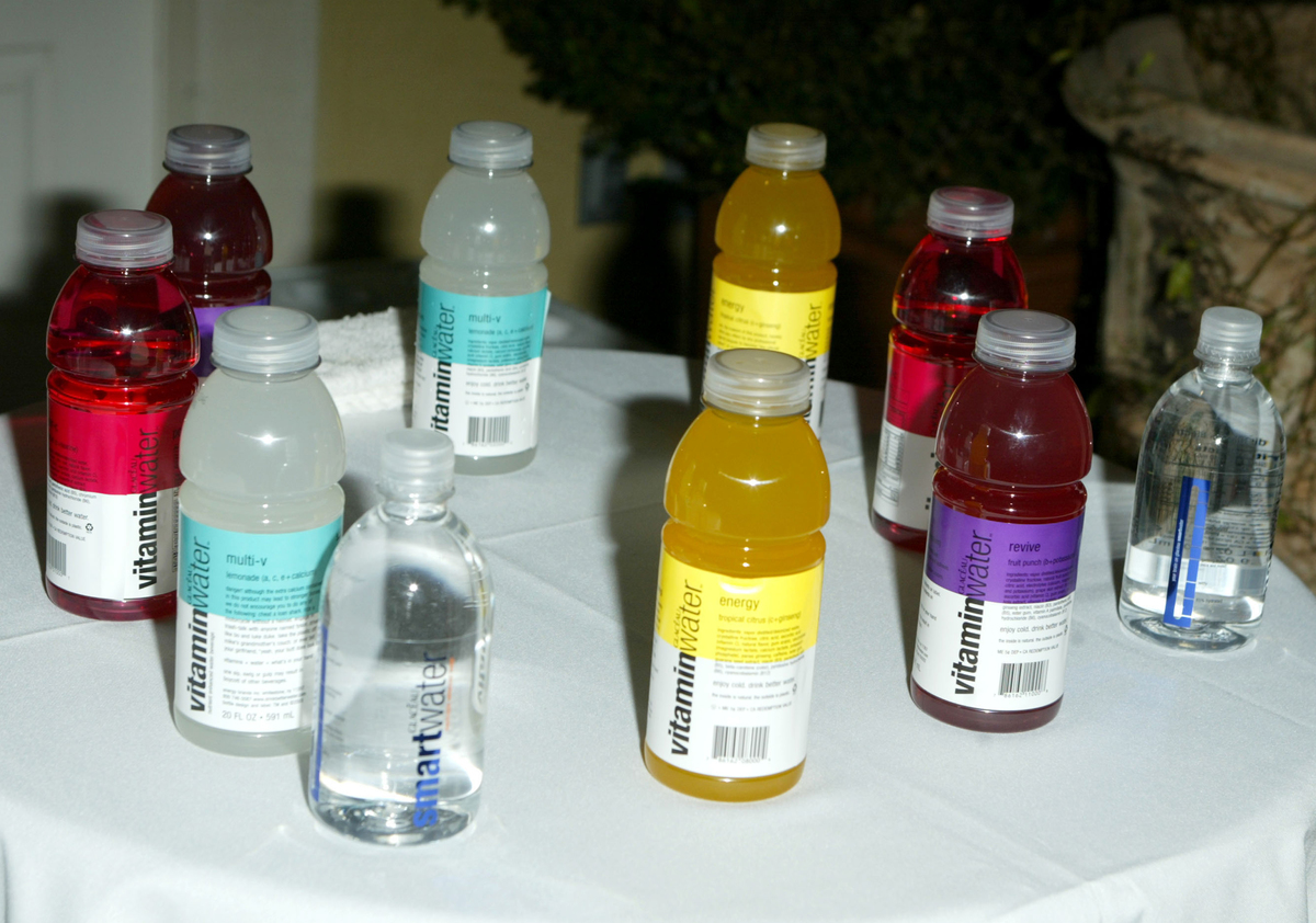 Several Vitamin Water bottles sit on a table.