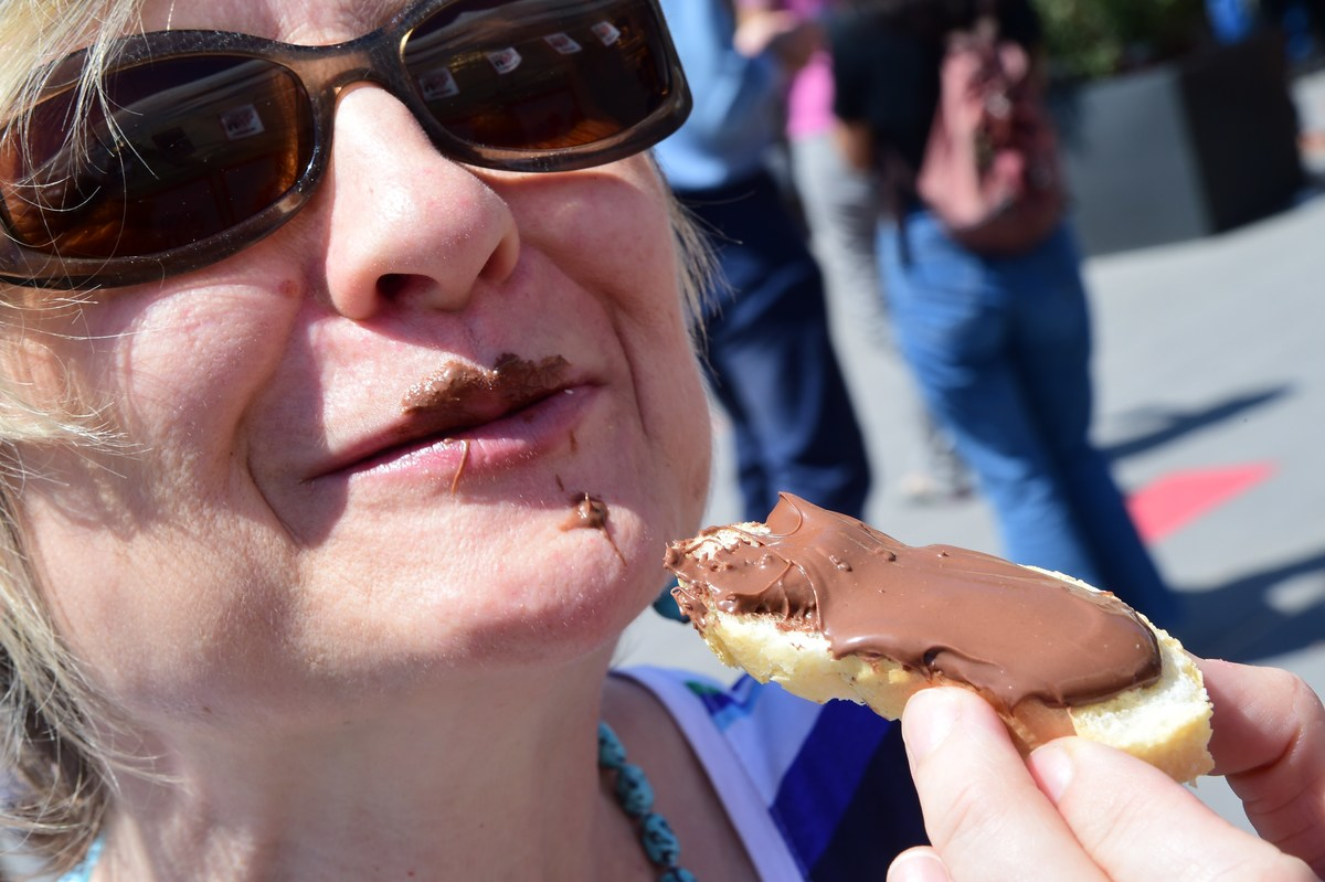 A woman eats a tartine of Nutella.