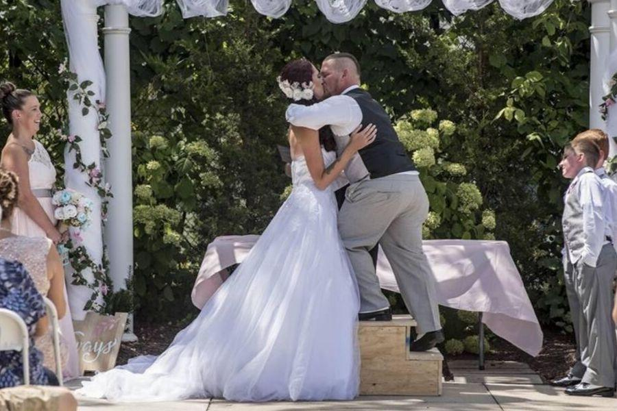 husband on step stool to kiss his wife at wedding