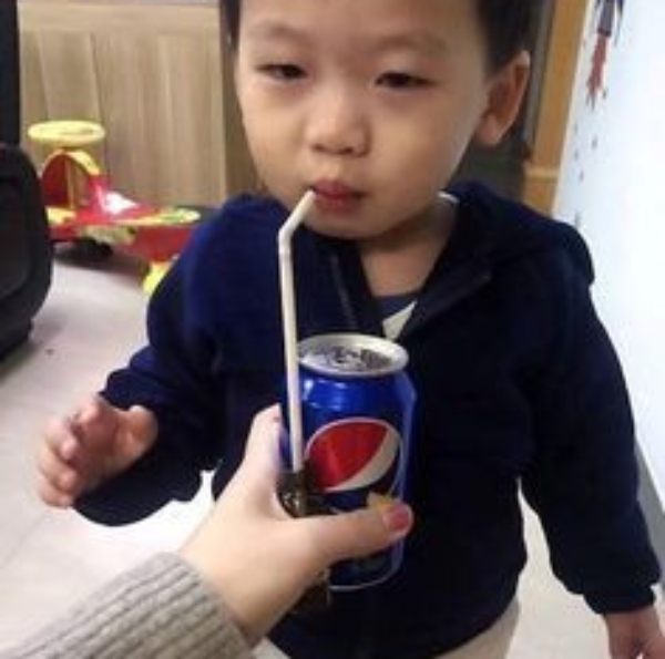 kid drinking medicine from straw but thinks its pepsi