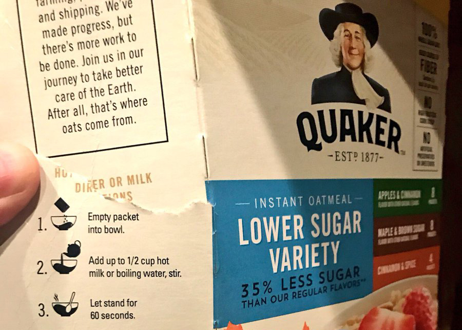 A man shows the instructions on an instant Quaker Oats box.