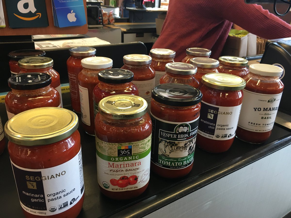 Several brands of pasta sauce sit on a table.