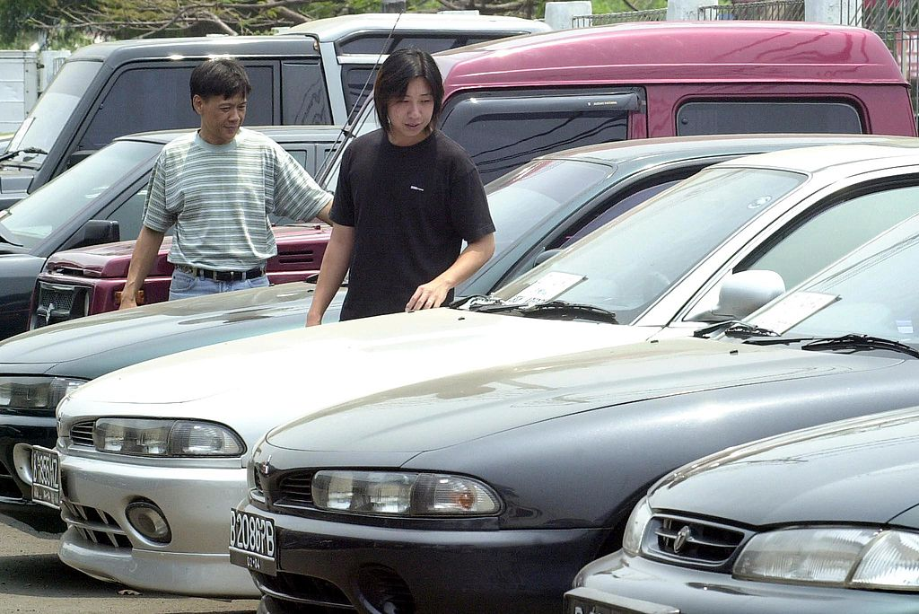 Two men look at used cars at a dealership