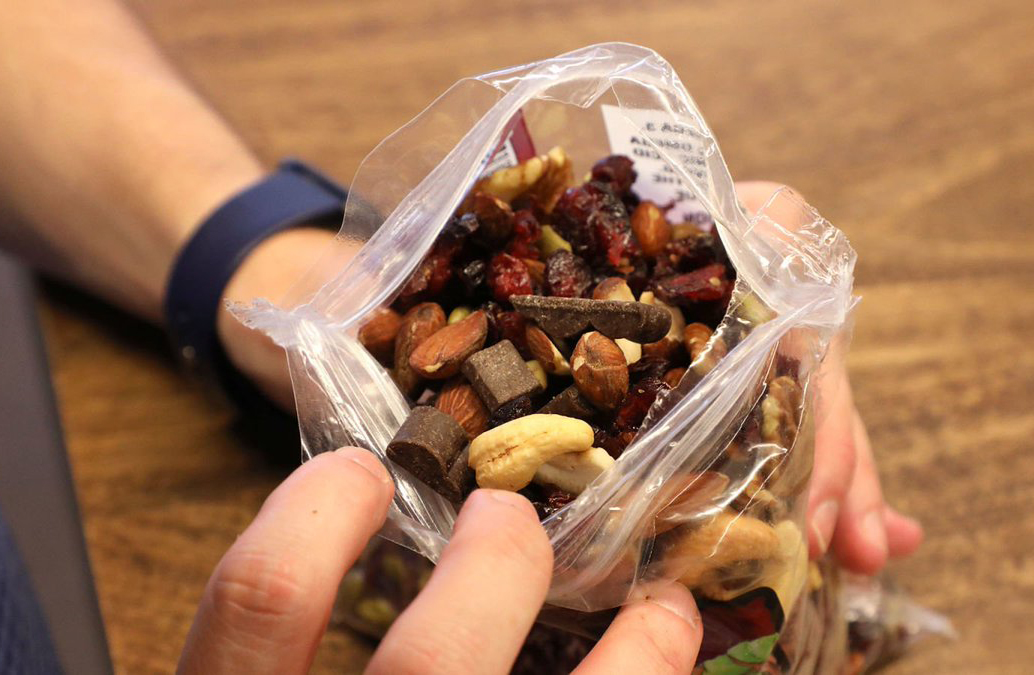 A person sifts through a trail mix bag of dried craisins, dark chocolate, almonds, and cashews.