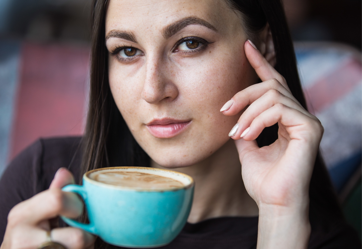 A woman drinks coffee from a blue mug.