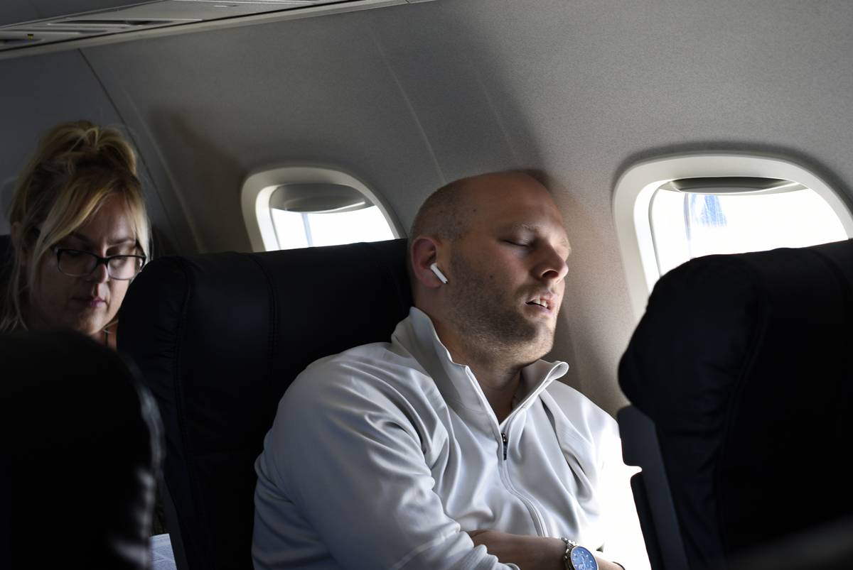 A passenger sleeps on a plane.