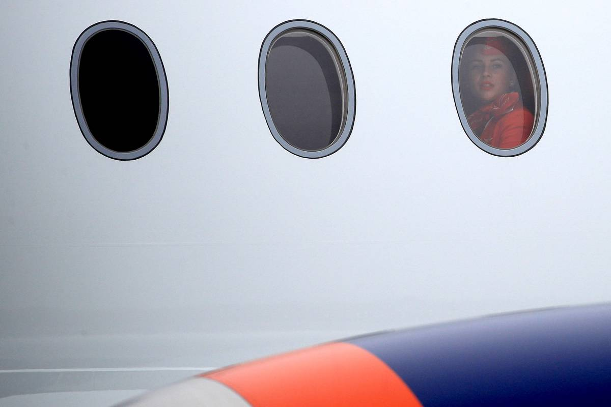 A passenger looks out of a plane window.