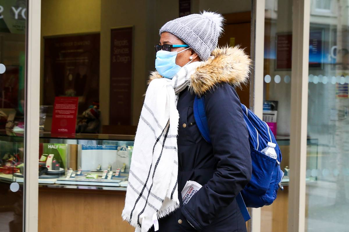 A woman wears a face mask while walking around London.
