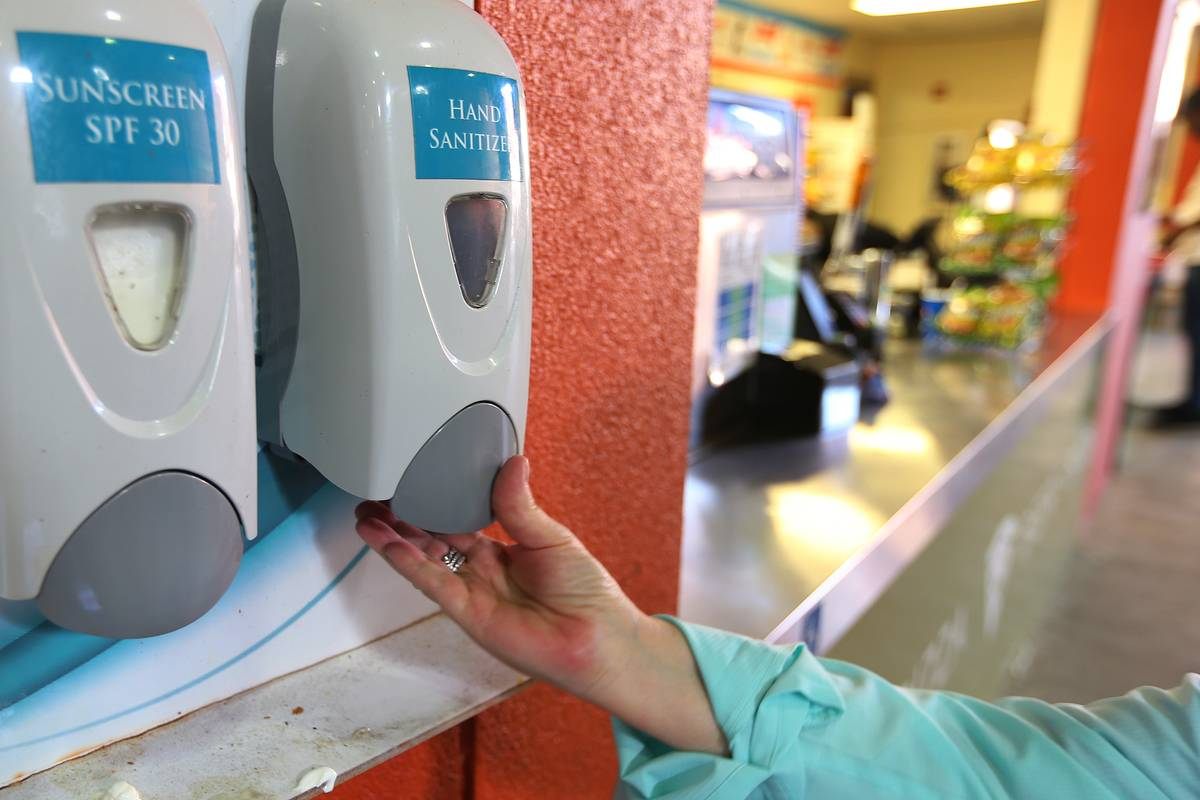 A woman receives hand sanitizer from a medical station.