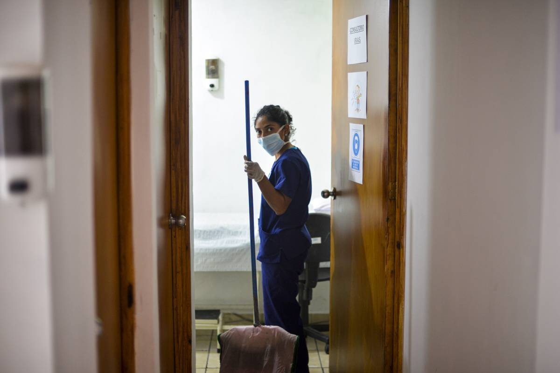 A woman in a mask cleans a hospital in El Salvador.