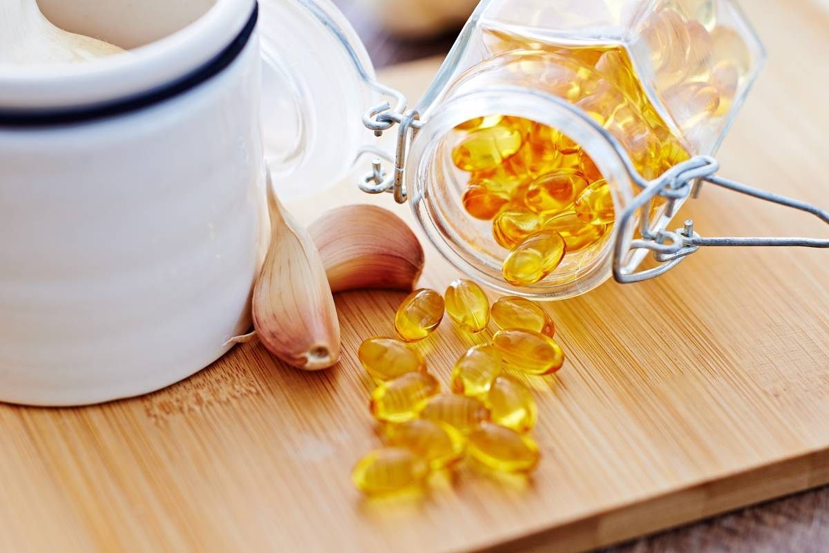 Vitamins pour out of an open glass container.