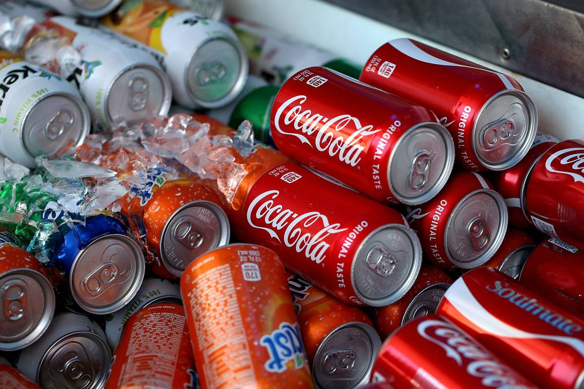 Cans of soda are displayed in a cooler.