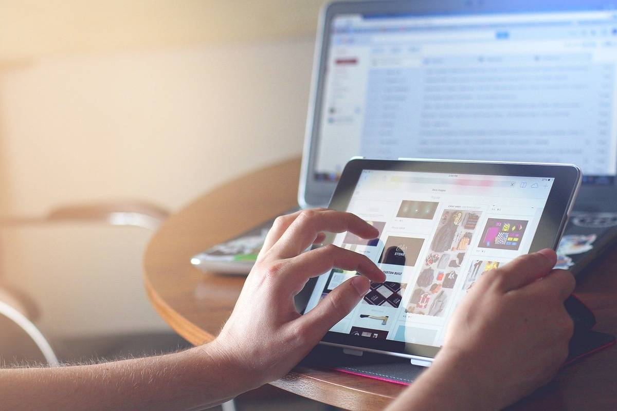 A person browses her iPad and computer.