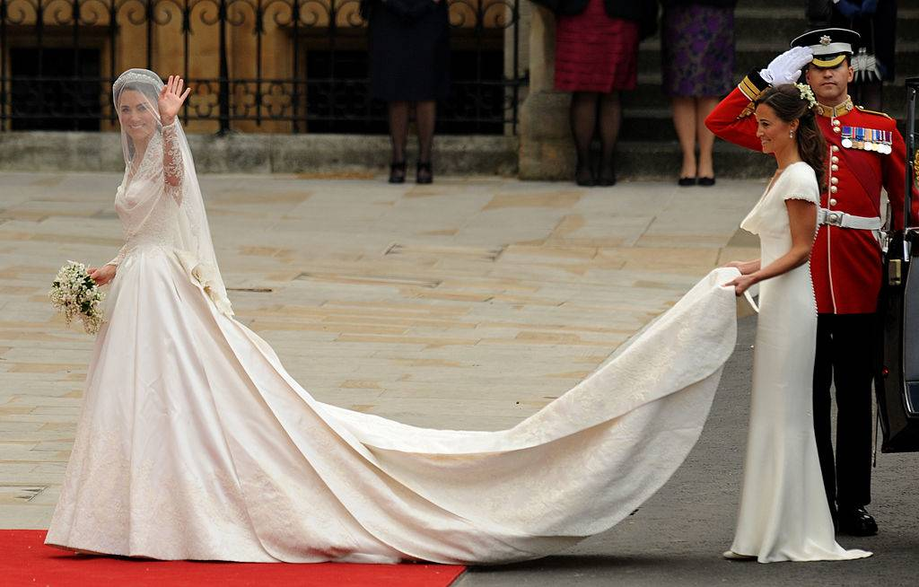 Kate Middleton waves as she arrives with her sister, the Maid of Honour Philippa Middleton at the West Door of Westminster Abbey