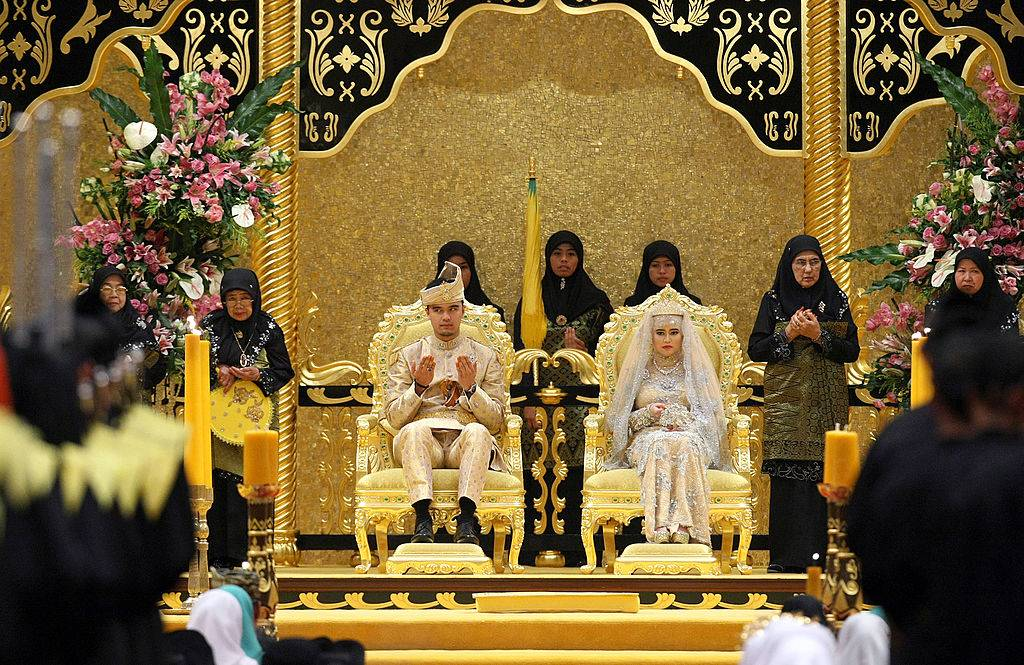 The Royal couple Princess Hajah Hafizah Sururul Bolkiah and her groom Pengiran Haji Muhammad Ruzaini (L) pray at the end of the sitting-in-state on royal dais ceremony