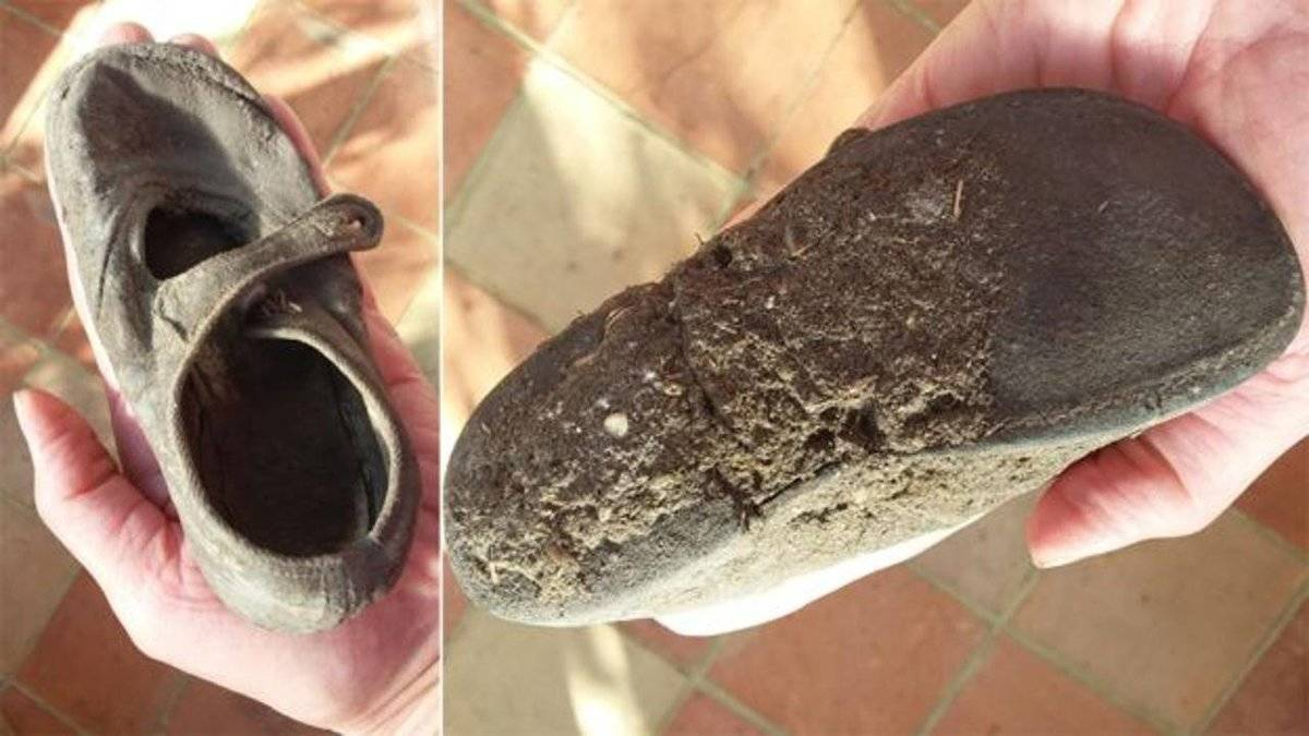 A woman holds a vintage shoe found inside of her wall.
