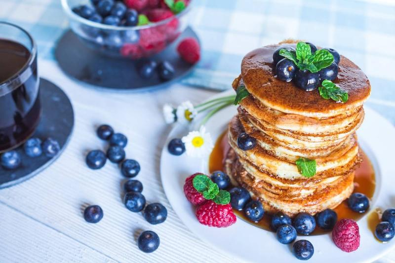 A large stack of blueberry pancakes is surrounded by blueberries.