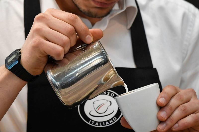 A barista pours cream into a coffee.
