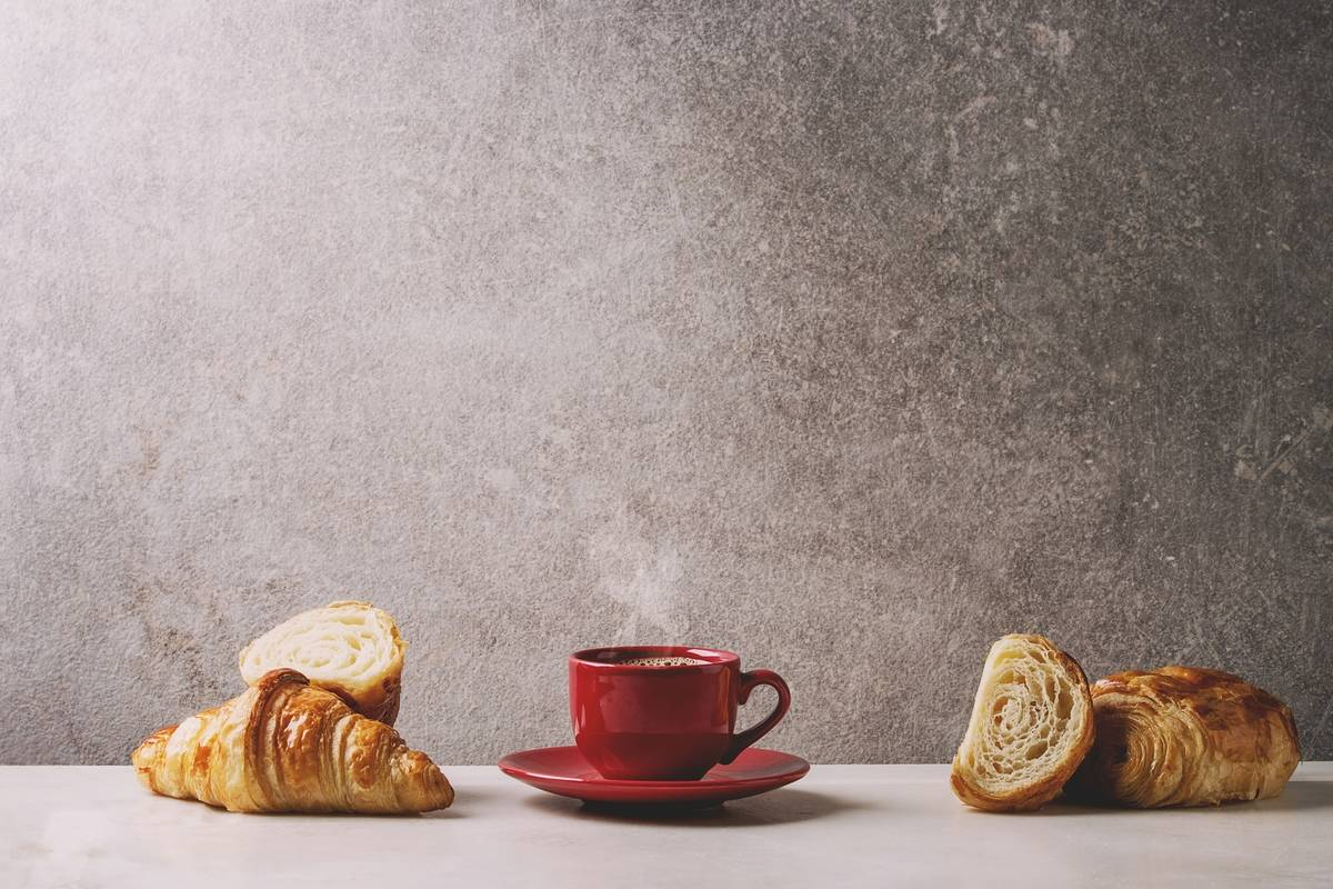 A red mug of coffee sits next to croissants.