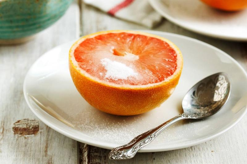 Half of a grapefruit with sugar on top is served for breakfast.