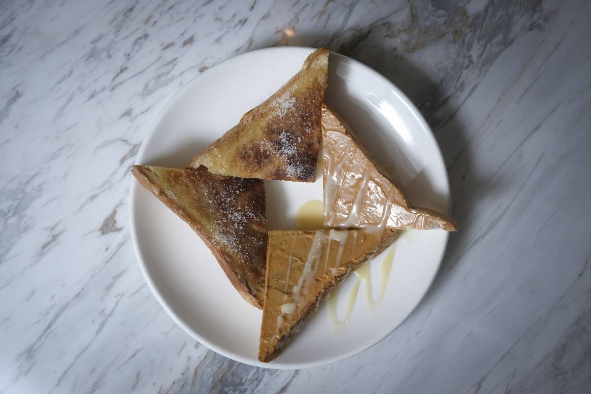 Triangle-shaped pieces of toast have peanut butter and condensed milk.