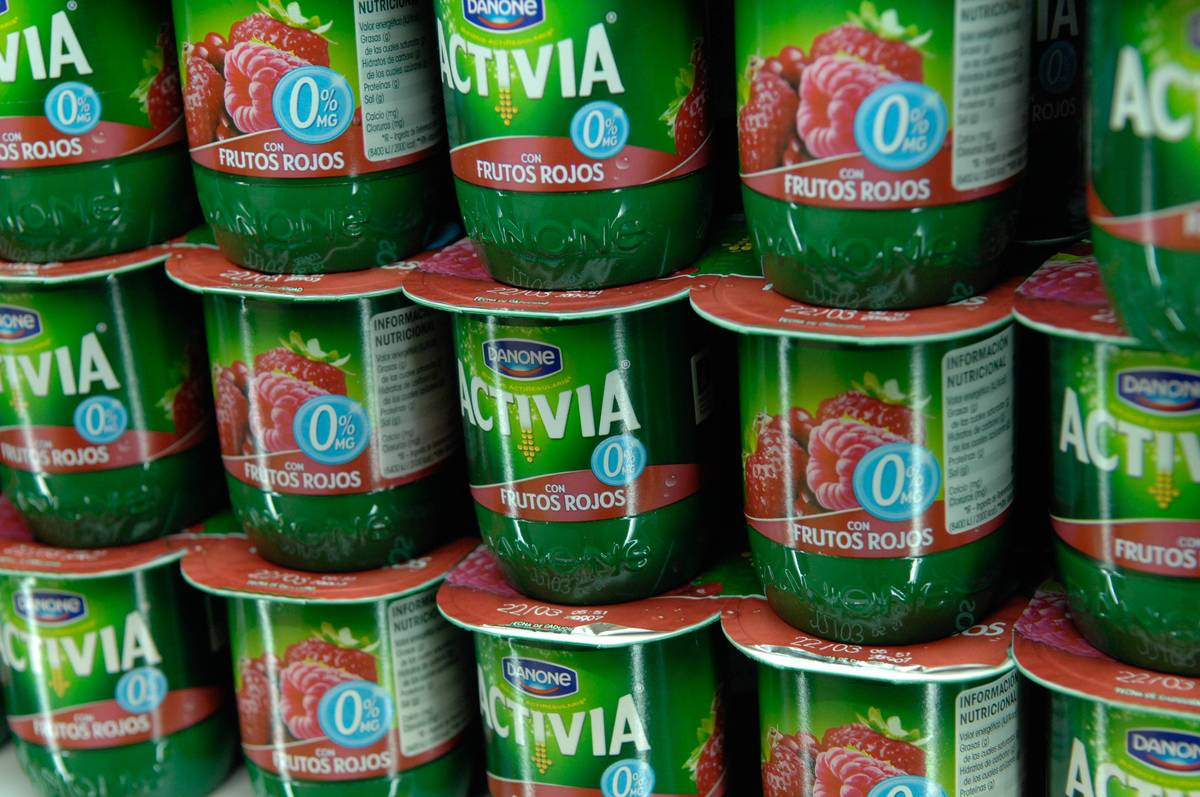 Activia yogurt containers are stacked in a grocery store.