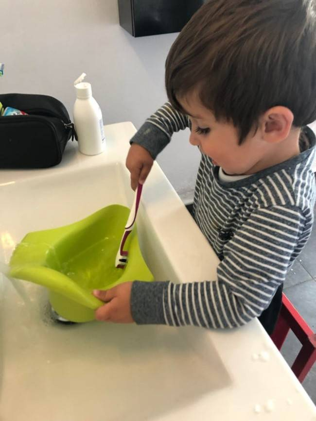 child cleaning his potty with parent's toothbrush